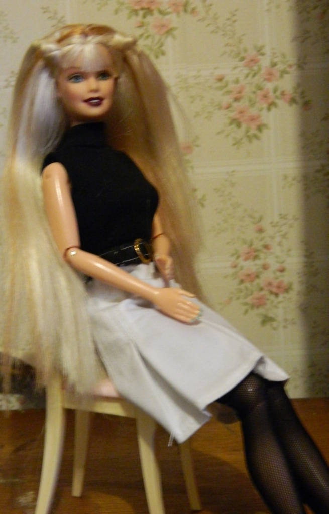 Elsa wears an unmarked black leotard, black stockings and belt and a whilte skirt with a Candi tag.