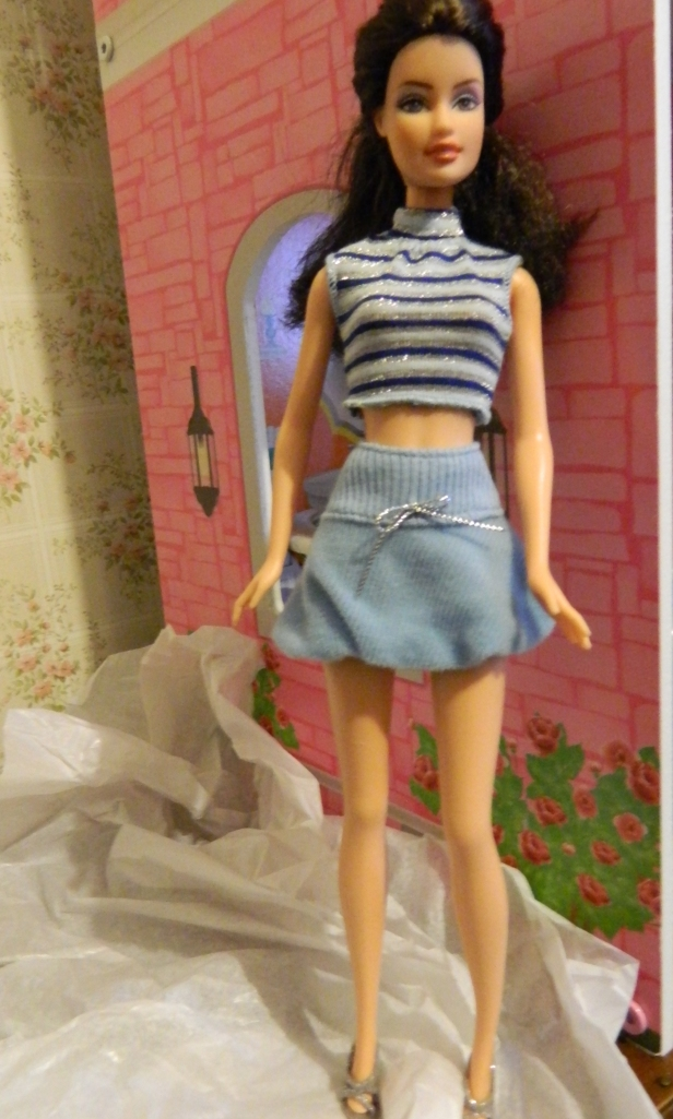 Trina wears the striped top, skirt and silver sandals.