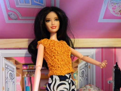 Marissa in an orange top knitted in 2 ply cotton on 2mm needles.