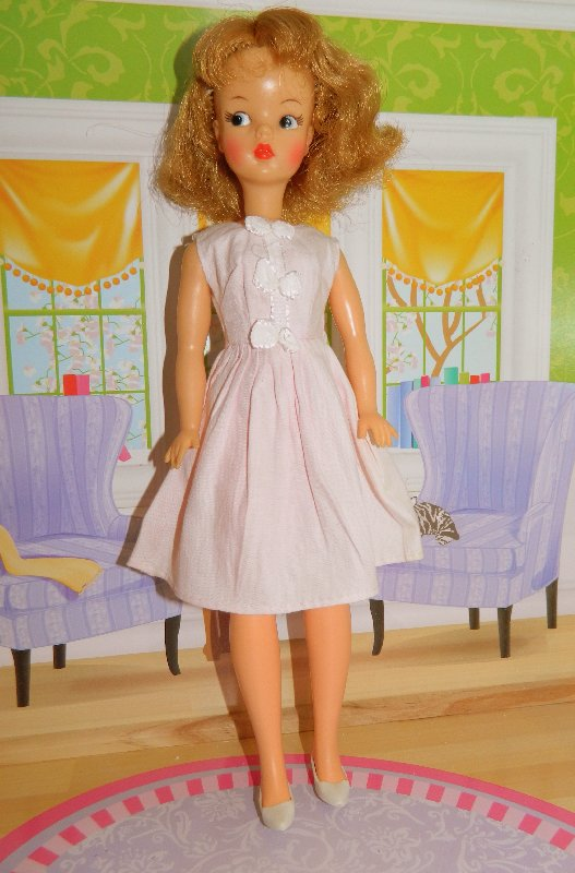 American Tammy wears a pale pink cotton dress.