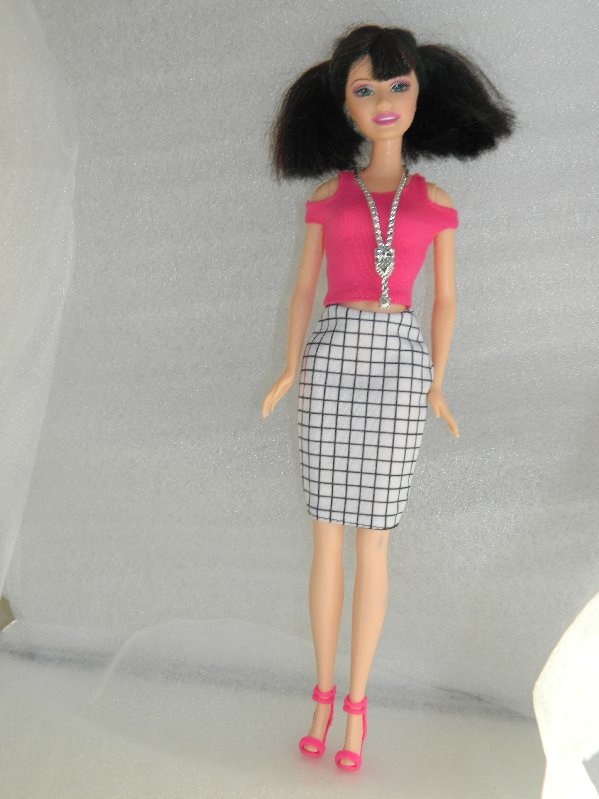 Robyn wears a pink top and a black and white check pencil skirt with pink sandals.