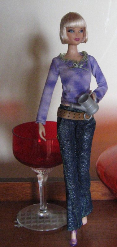 Becky is ready for the garden in jeans and mauve top with green trim.