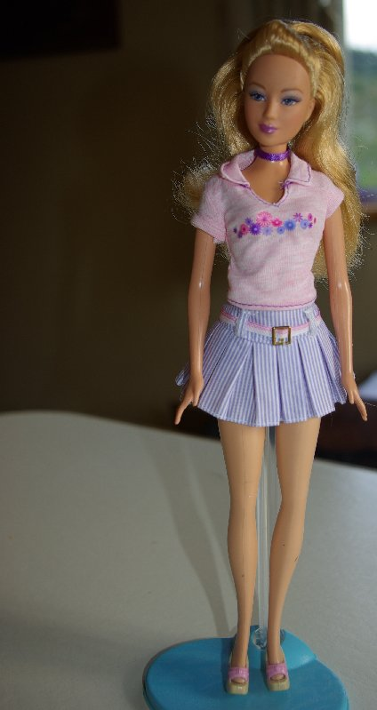 Diana in pleated skirt and pink top.