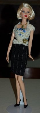 Jan wears the lacy blouse with a black and white pin stripe skirt.