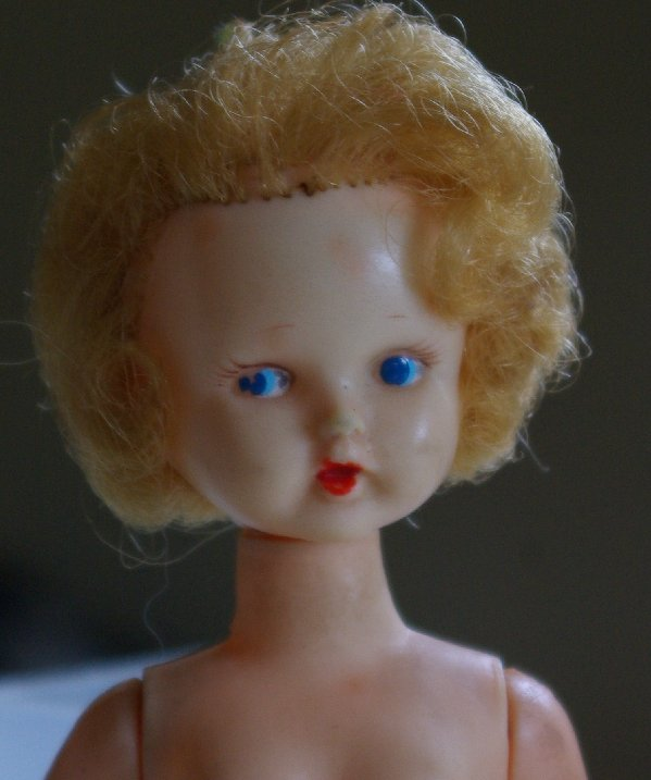 doll with painted blue eyes and rooted blonde hair