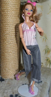 Sandy wears a pink pleated top and grey denim cropped jeans.