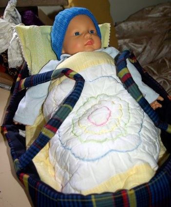 Redressed in baby clothes with a cot quilt and blanket.